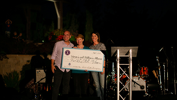Orville and Heidi Thompson presenting a check to the Women's and Children's Alliance.