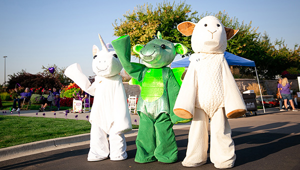 Scentsy Buddies mascots waving to cars on Eagle road.
