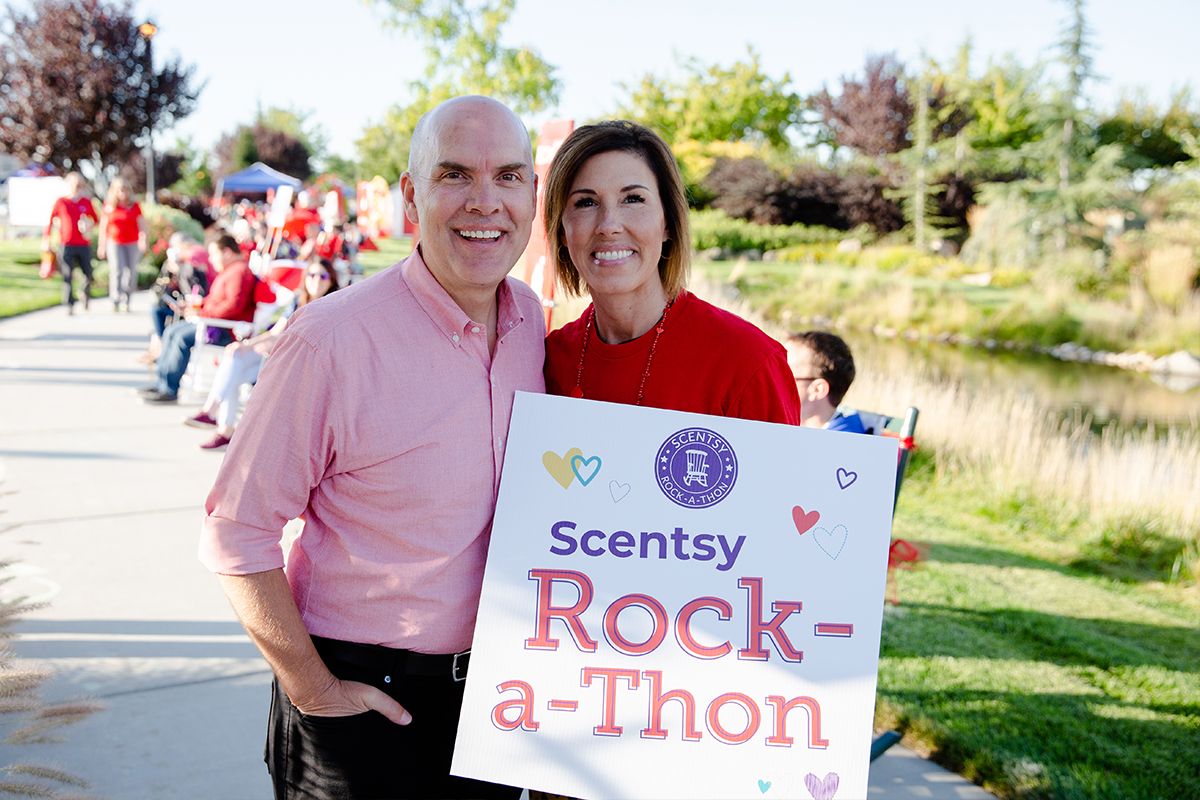 Orville and Heidi Thompson holding Scentsy Rock-a-Thon sign