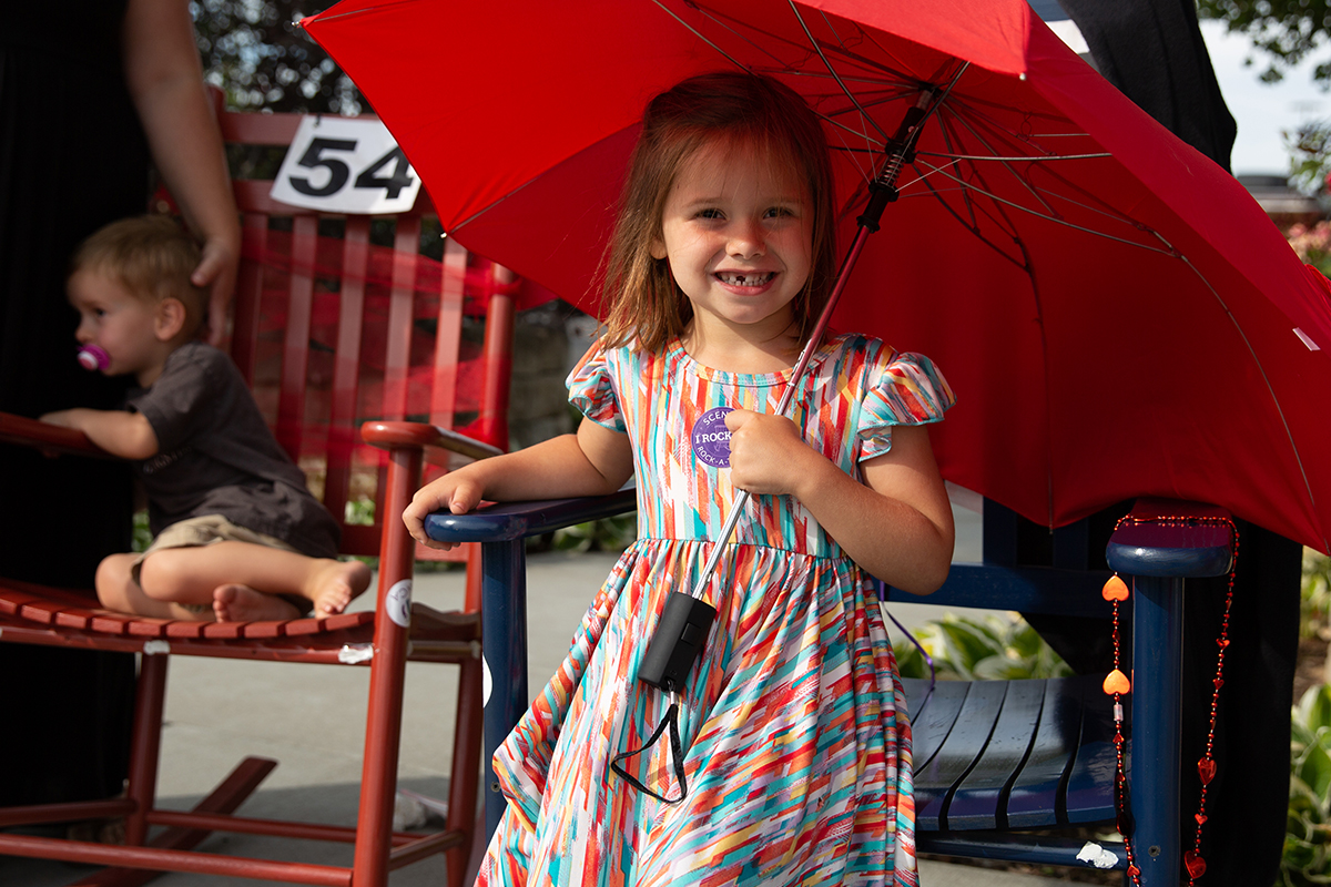 little girl in rocking chair holding a red umbrella