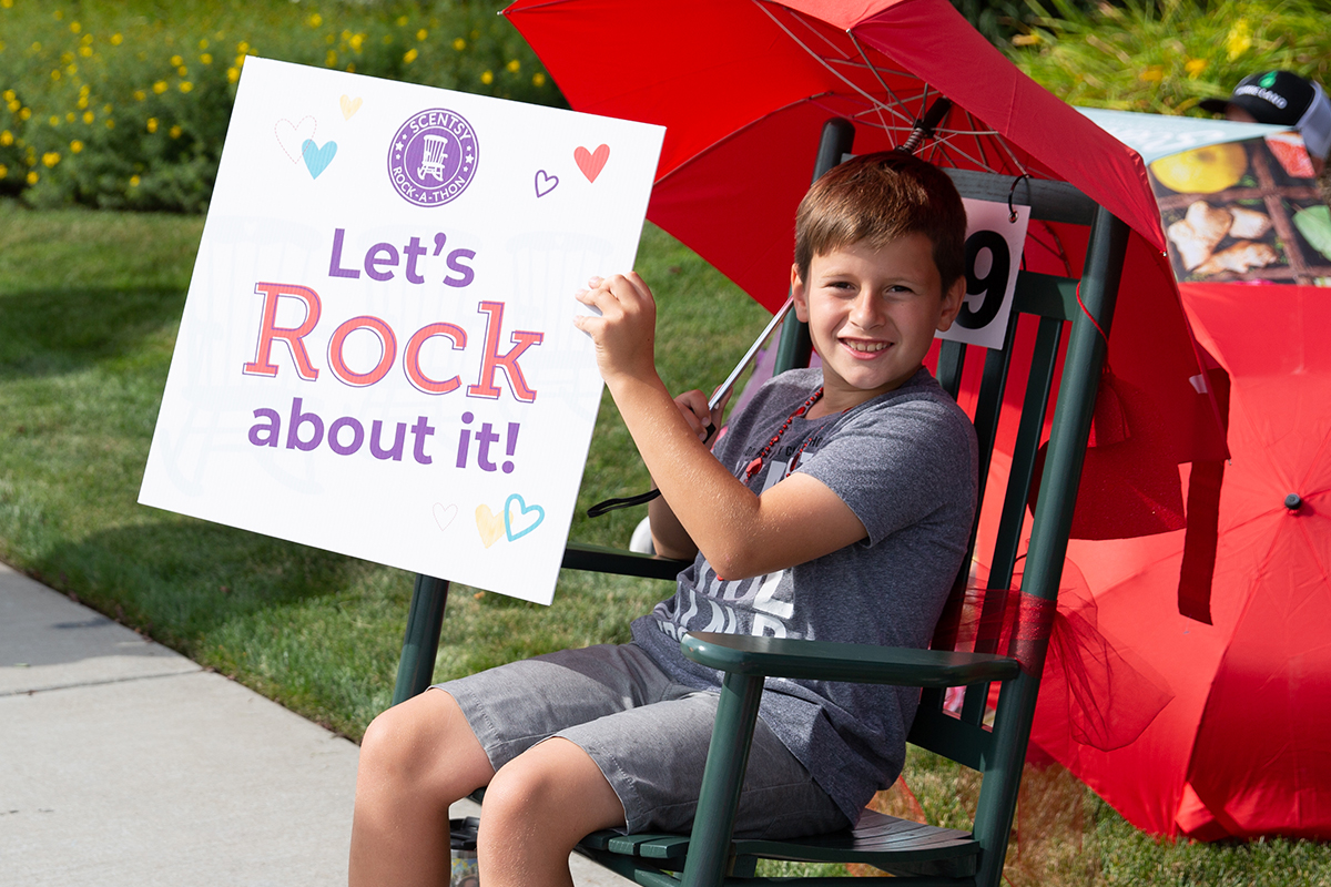 """little boy in rocking chair holding a sign that says """"Let's Rock about it!"""""""