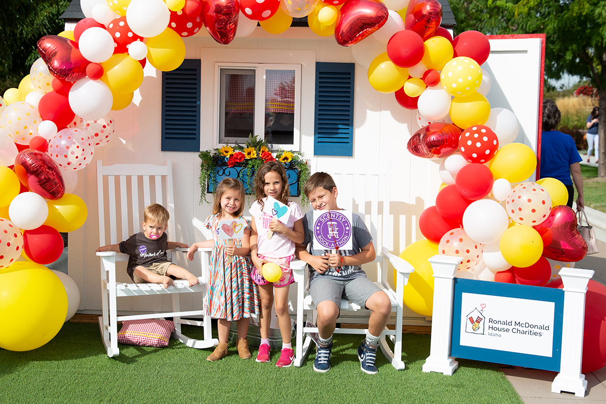 kids sitting in front of Ronald McDonald House playhouse
