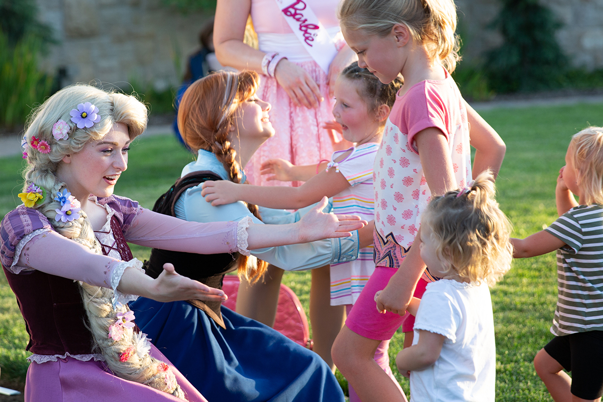 princesses hugging and interacting with little girls