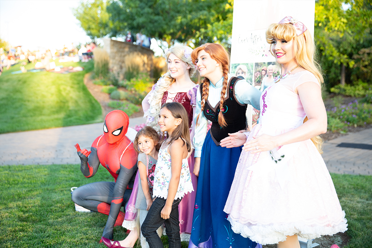 spiderman and princesses posing with two little girls