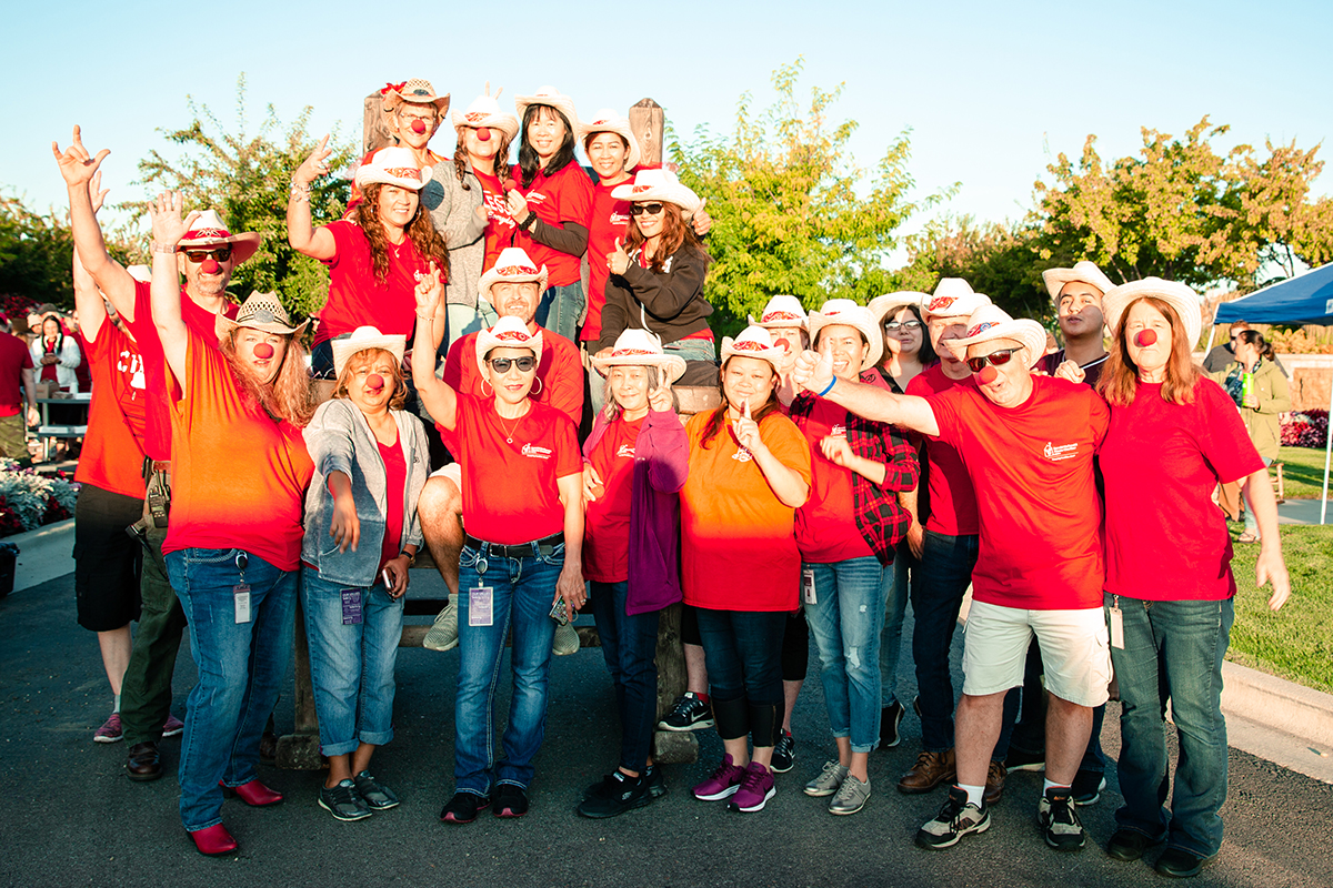 big group of people with red shirts and wearing red noses