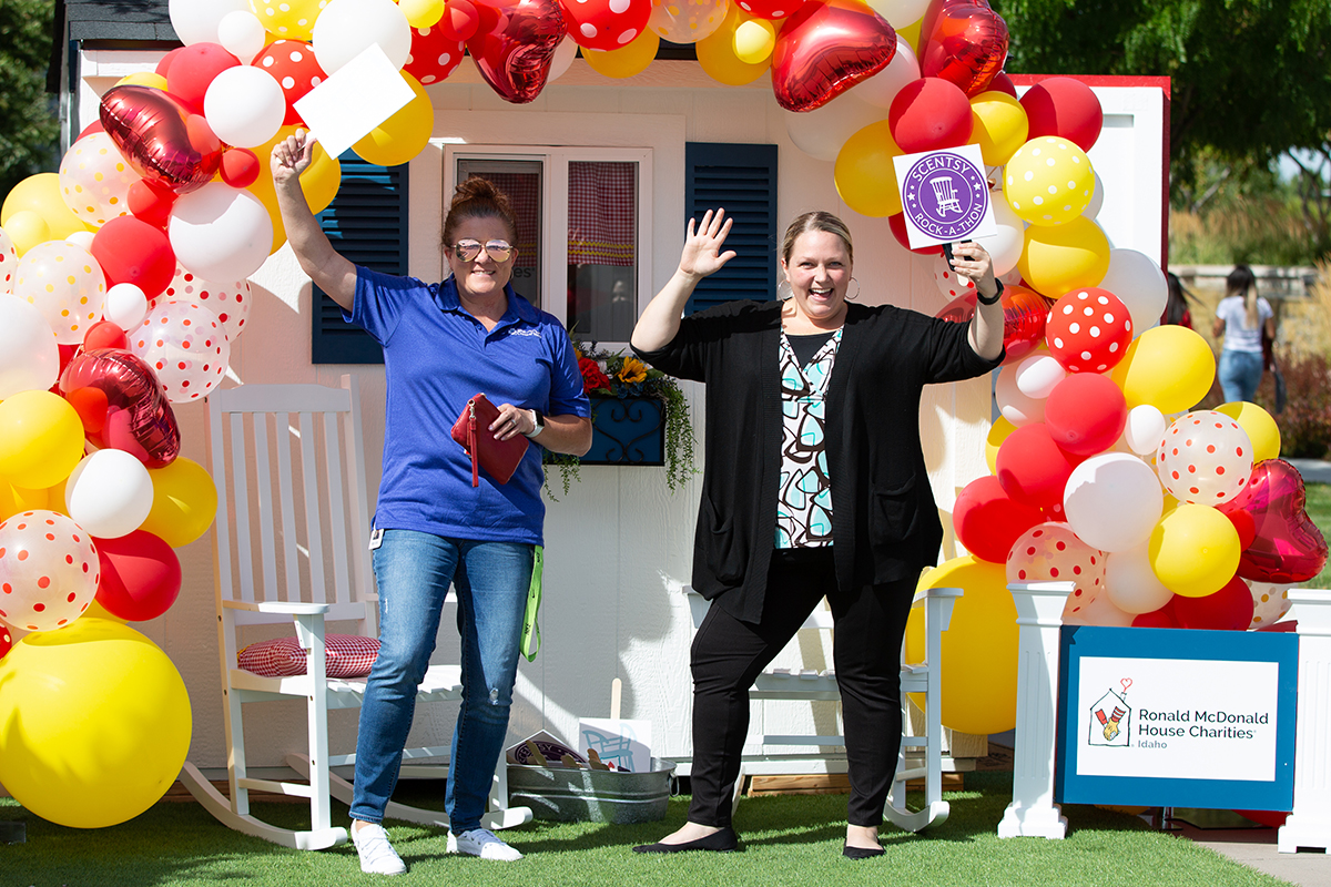 two women posing in front of Ronald McDonald House playhouse