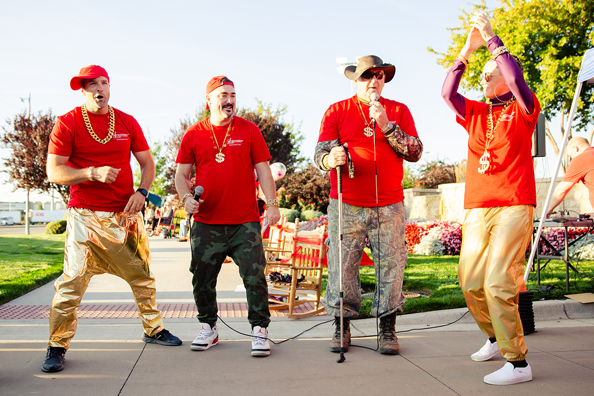 four people with red shirts and gold pants performing a rap song