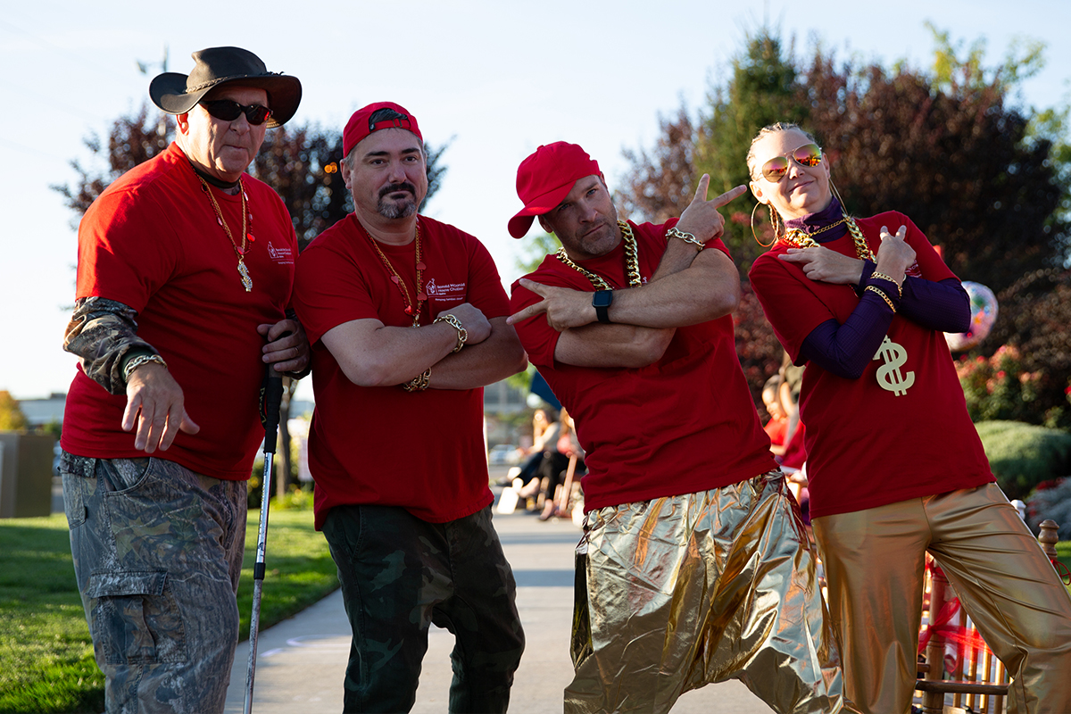 four people dressed as wrappers in red shirts and gold pants posing