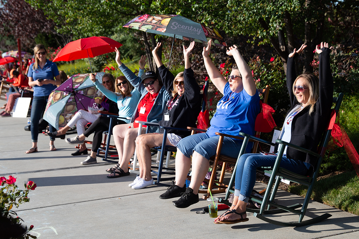 group of people siting in rocking chairs cheering with their hands up