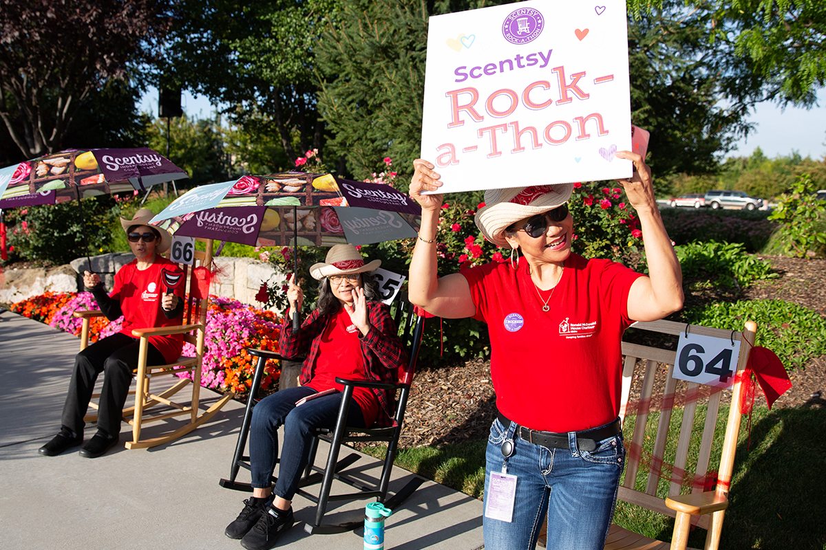 """standing woman in red shirt and cowboy hat holding up a sign that says """"Scentsy Rock-a-Thon"""" with another woman sitting in rocking chair"""