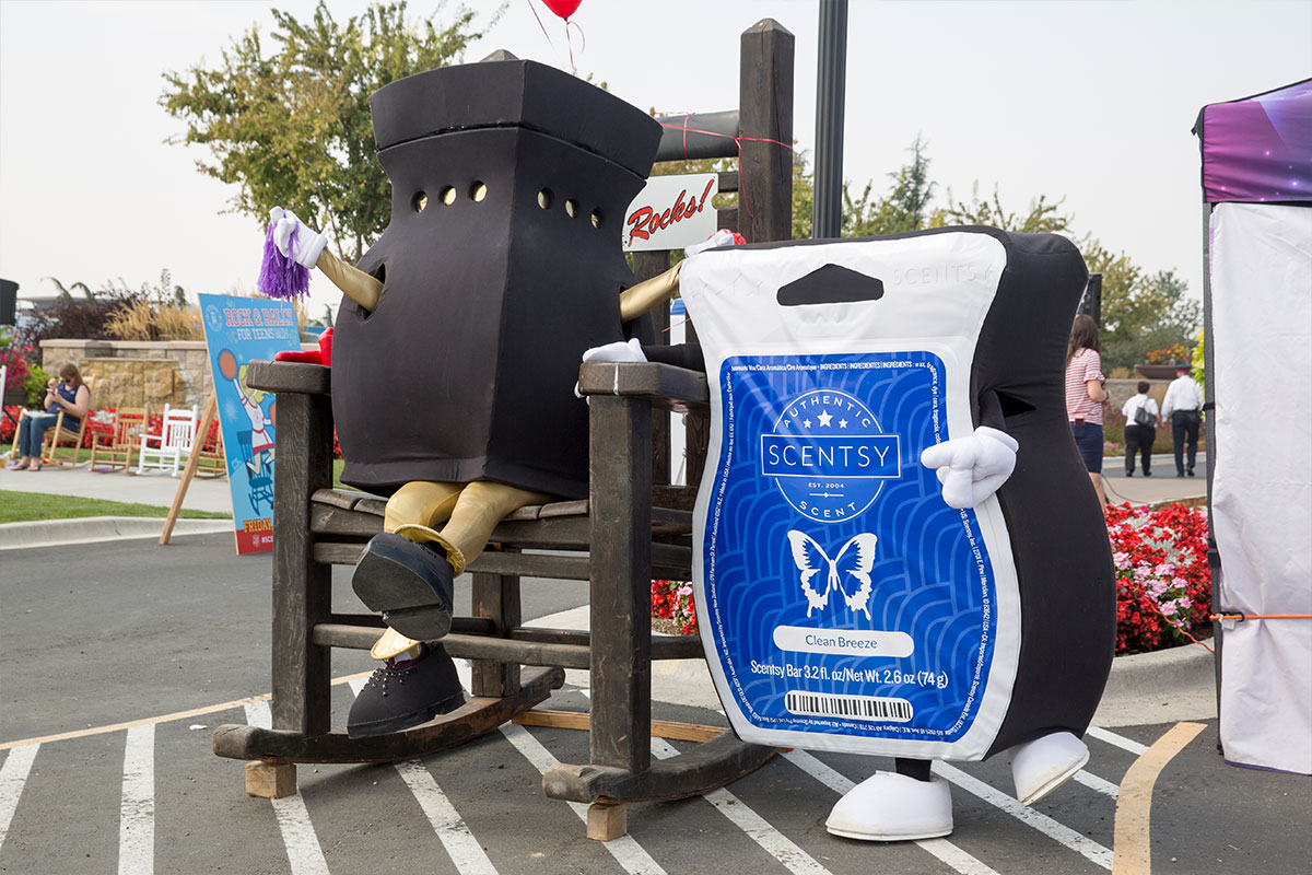 warmer and wax bar characters posing with oversized rocking chair