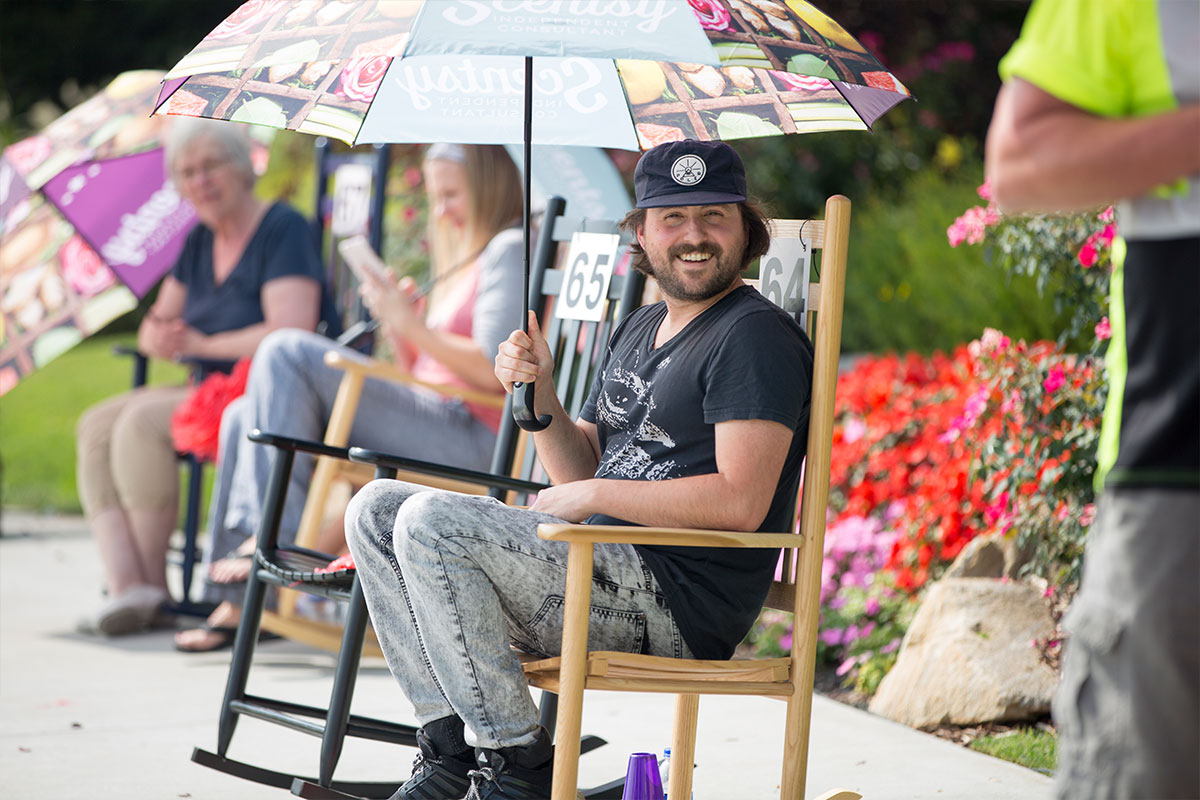 man holding an umbrella while sitting in a rocking chair