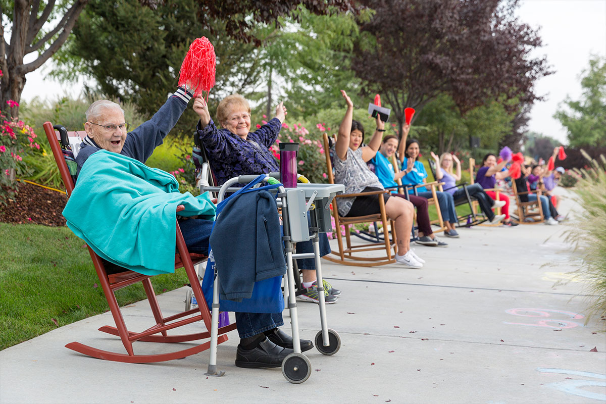 several people sitting in rocking chairs along sidewalk