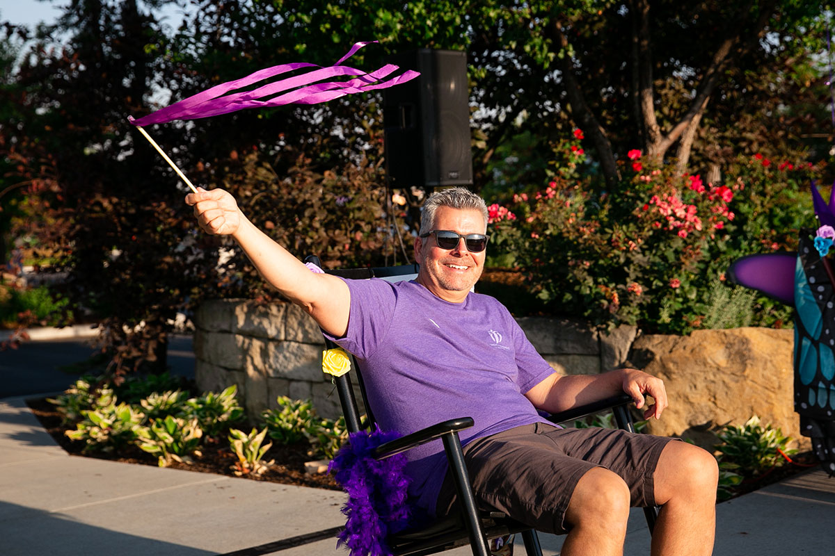 man waving a purple ribbon while sitting in a rocking chair