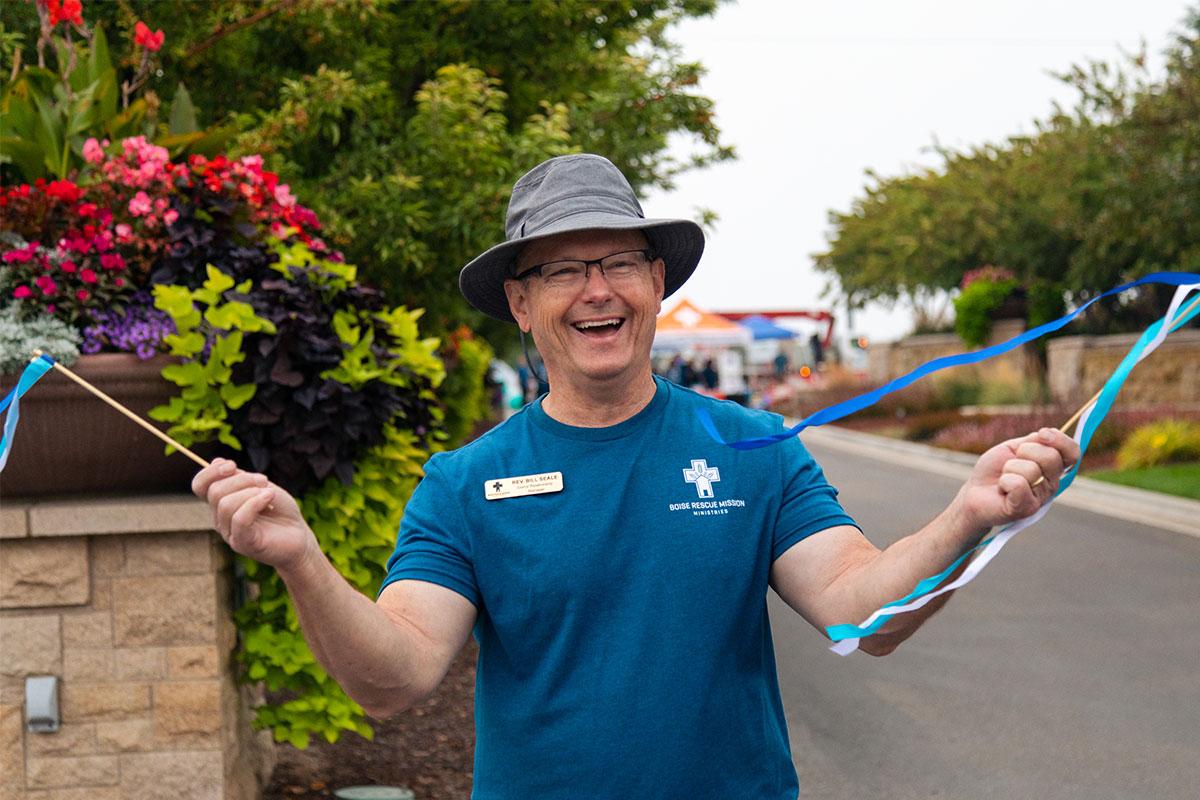 man in brimmed hat waving streamer sticks