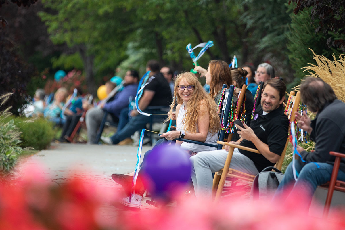 many people sitting and rocking in rocking chairs while smiling, laughing and talking