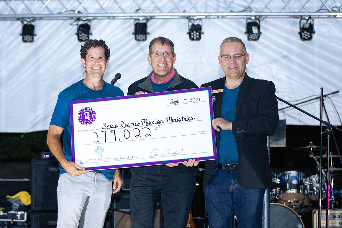 three men standing and holding large check for $279,022