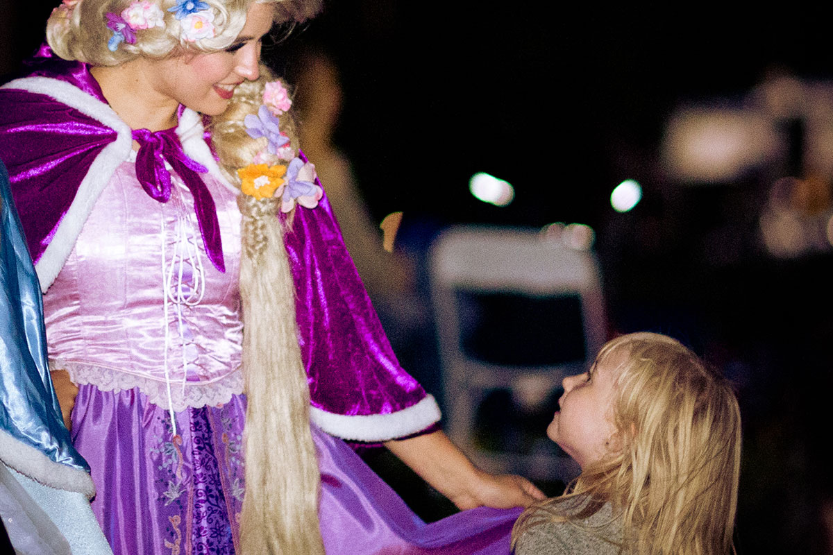 woman dressed up as princess talking with little girl