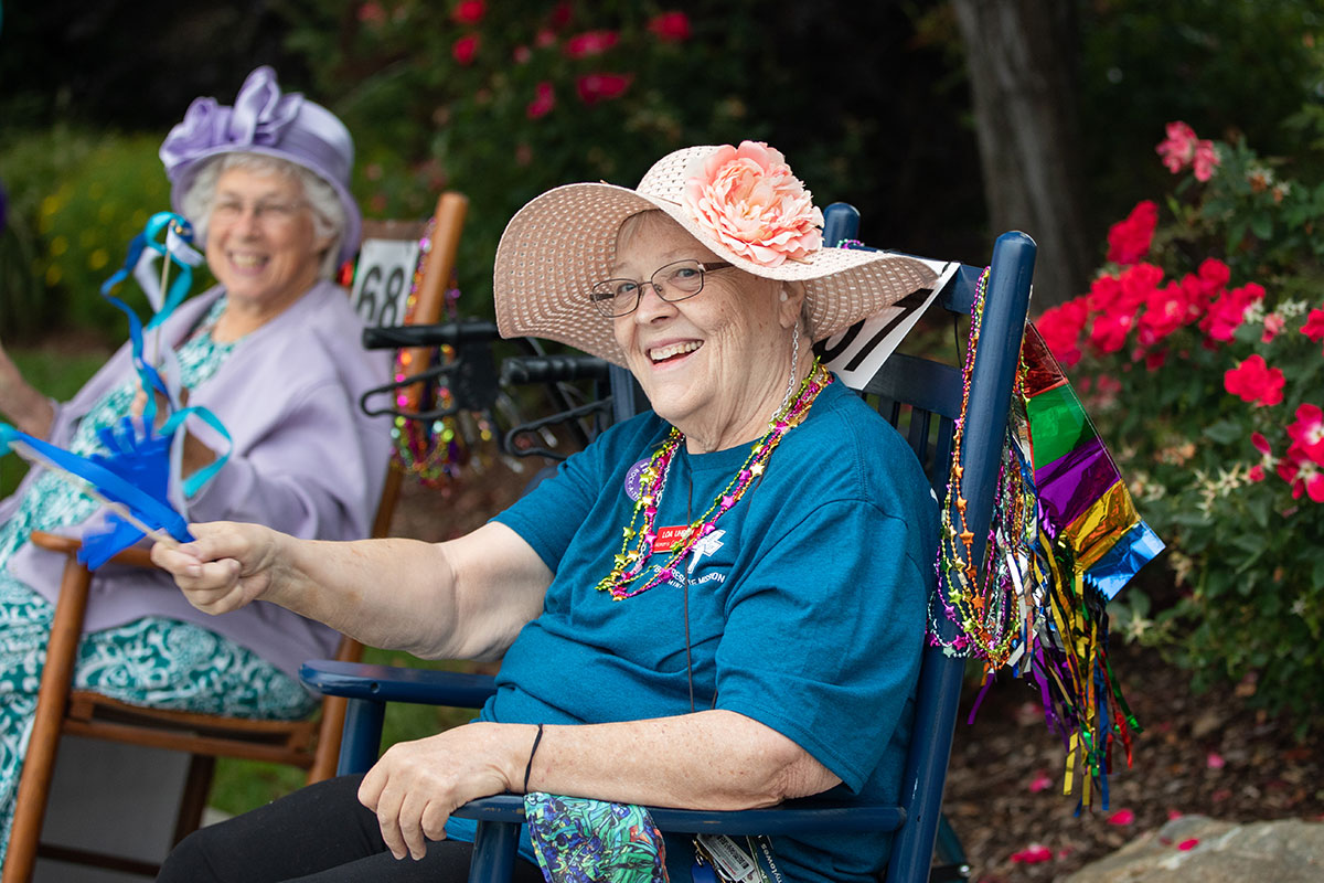 two smiling elder women with sun hats sitting and rocking in rocking chairs