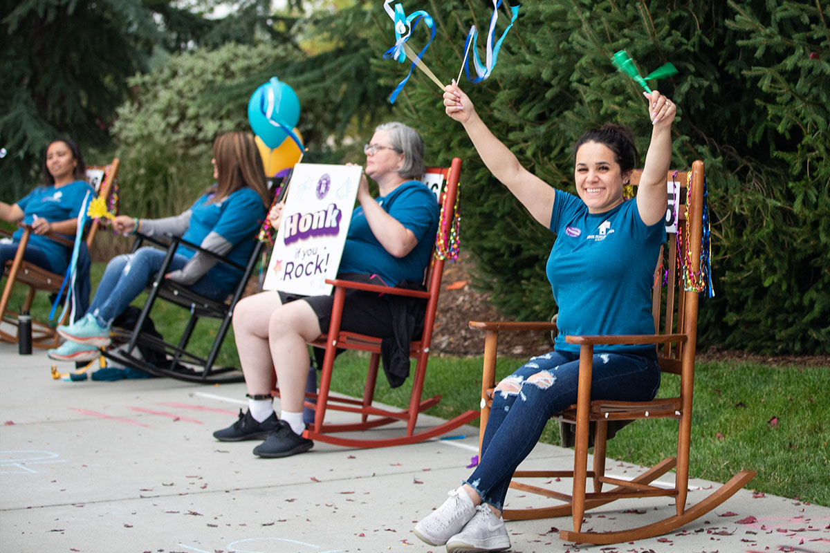 many people smiling and waving while sitting and rocking in rocking chairs