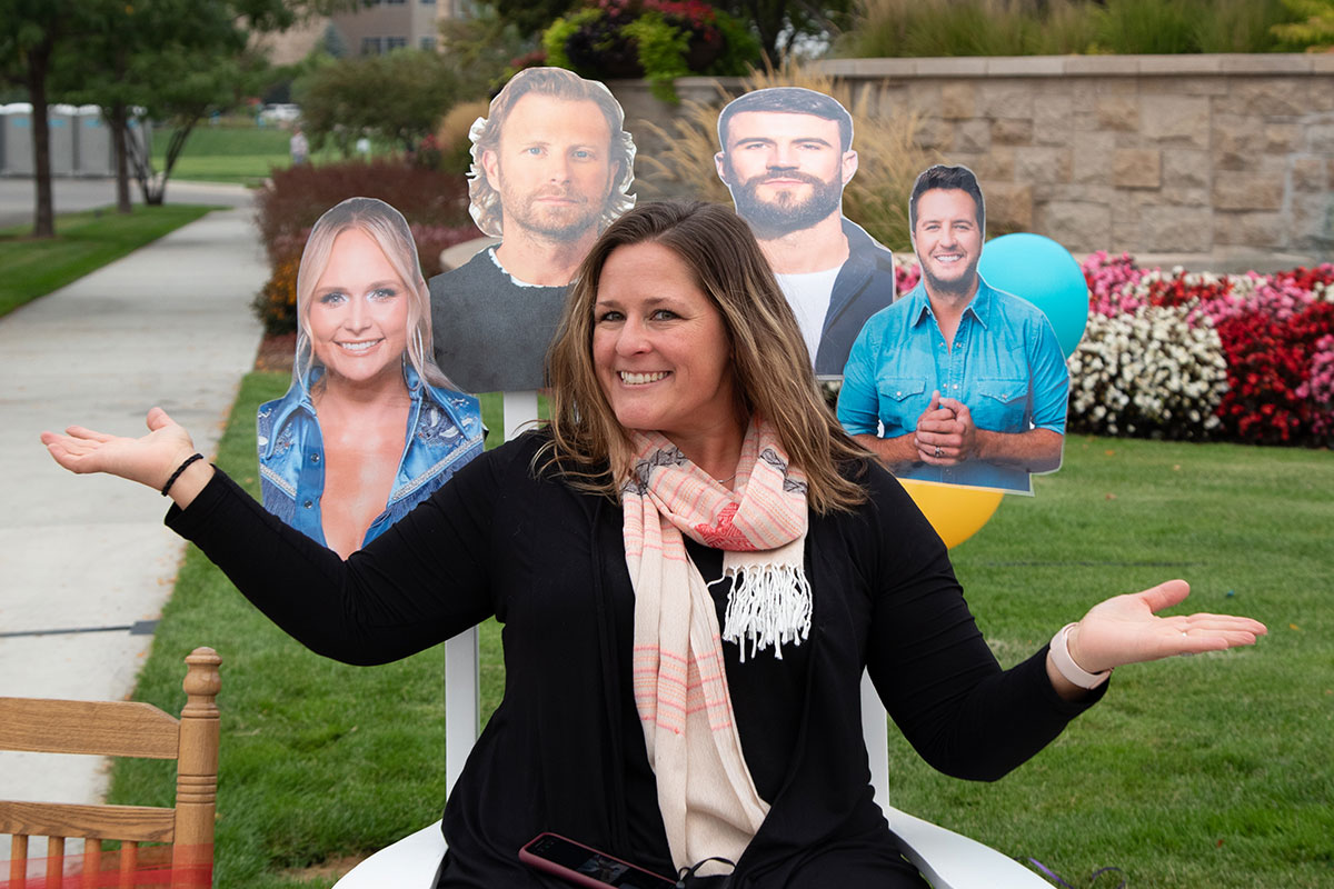woman sitting in rocking chair with cardboard cutouts of celebrities behind her