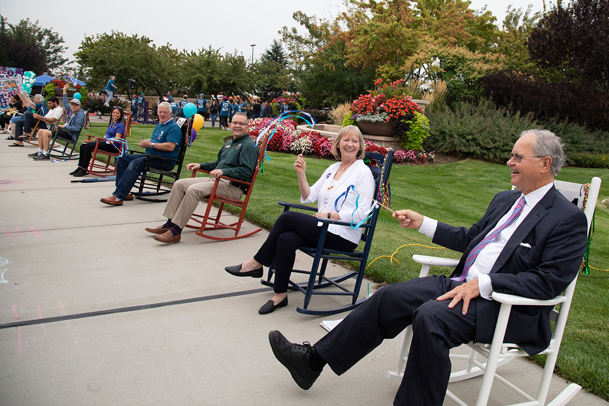 many people sitting in rocking chairs, smiling and waving