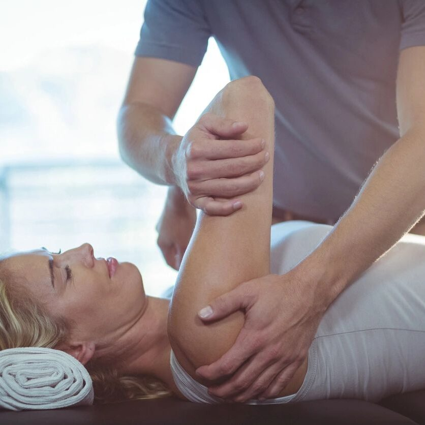 Patient lying on back while physical therapist uses manual physical therapy to manipulate her shoulder