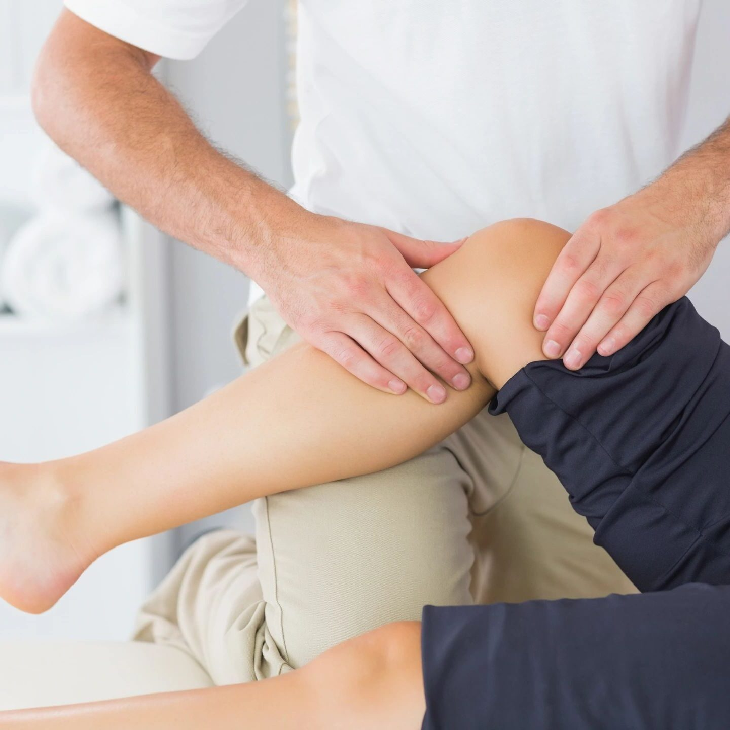 Physical therapist treating knee of patient who is lying down with leg slightly elevated using physical therapy techniques