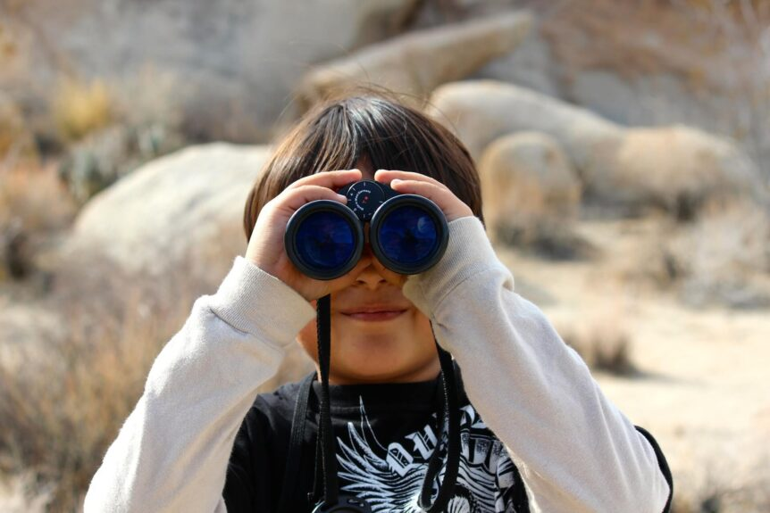 child looking through binoculars makes a parent ask does my child have vision problems