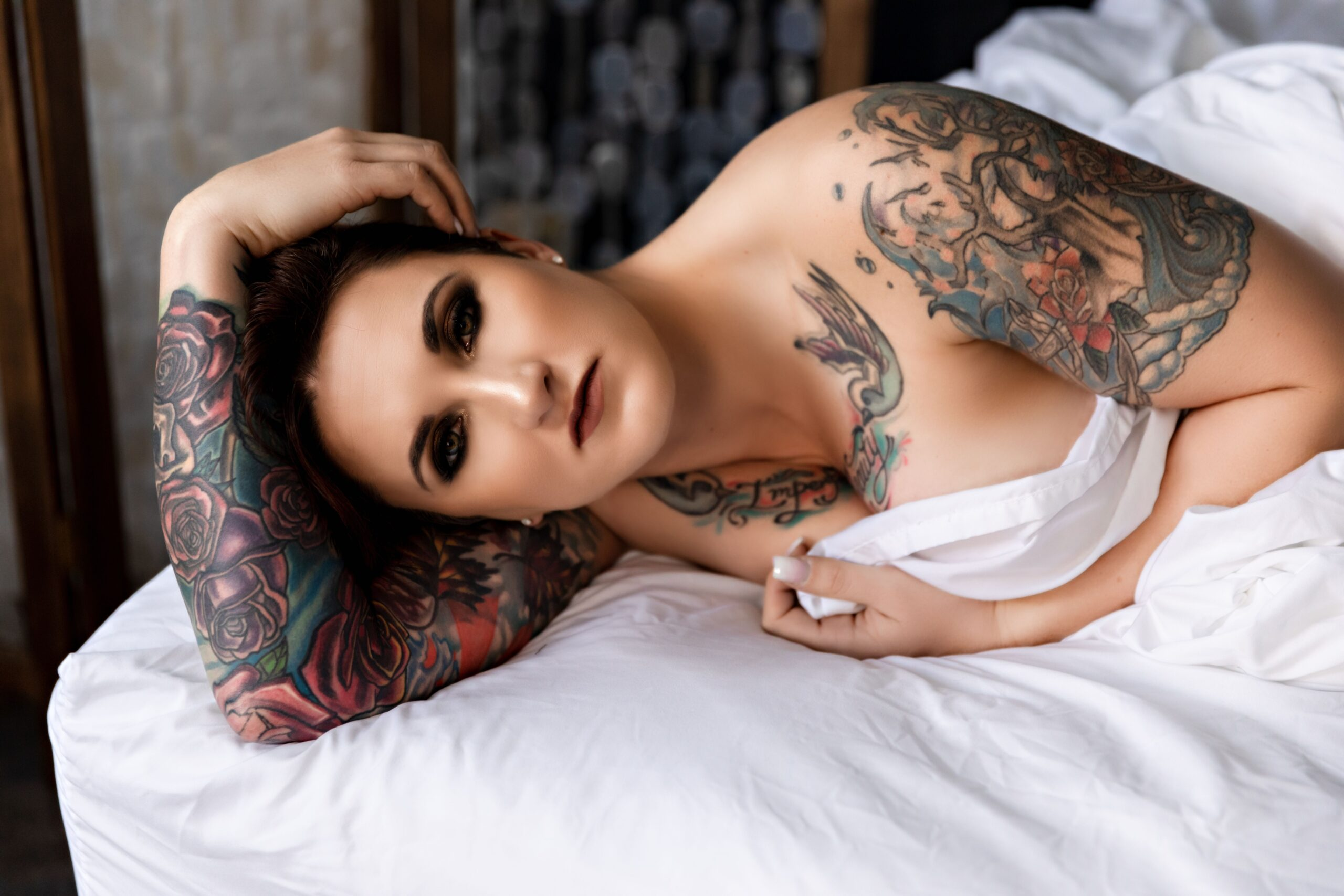Tattoo babe in white sheets