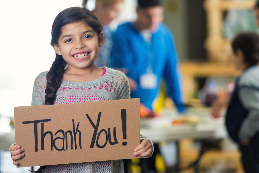 Cute Hispanic girl is holding a cardboard sign with 'Thank You!' witten on the board. She and her family are in a soup kitchen or food bank. She is smiling at the camera. Her brown hair is in a braid. Volunteers ar serving her family in the background. Focus is on the girl and the sign.