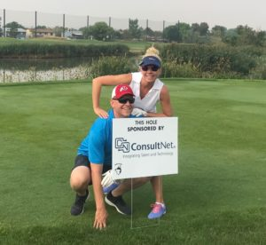 ConsultNet employees stand behind ConsultNet sponsorship sign at StoneBridge Golf Course, SLC