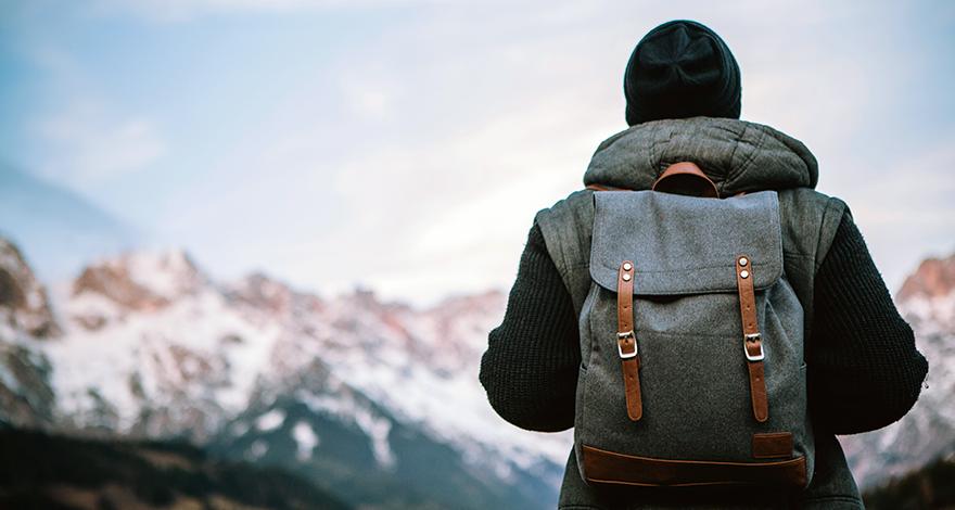 man backpacking facing mountains