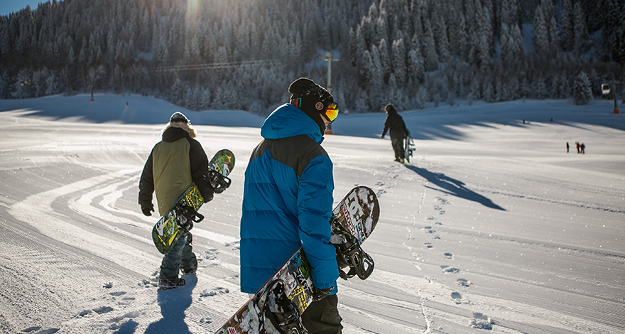 three snowboarders hiking up a mountain