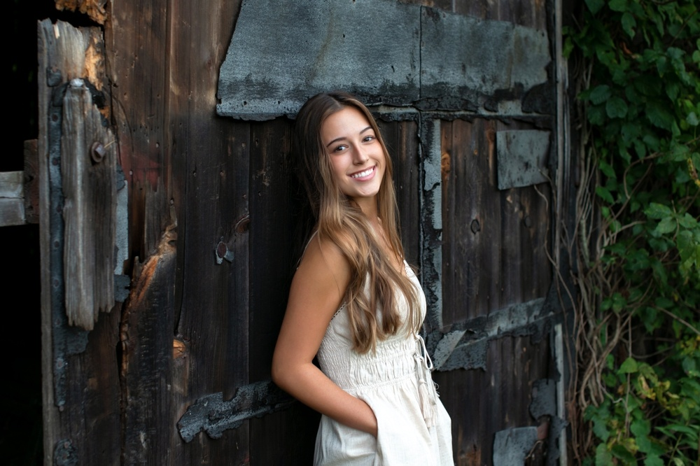 2021 ct senior portraits session leaning against old barn door at northwest park, ct
