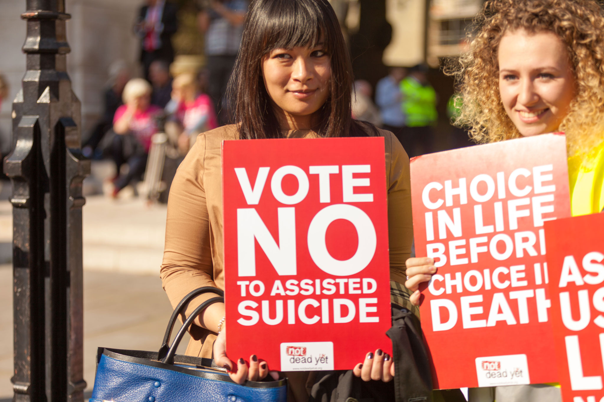 Two young women hold signs opposing doctor-assisted suicide at a protest held by Not Dead Yet UK.