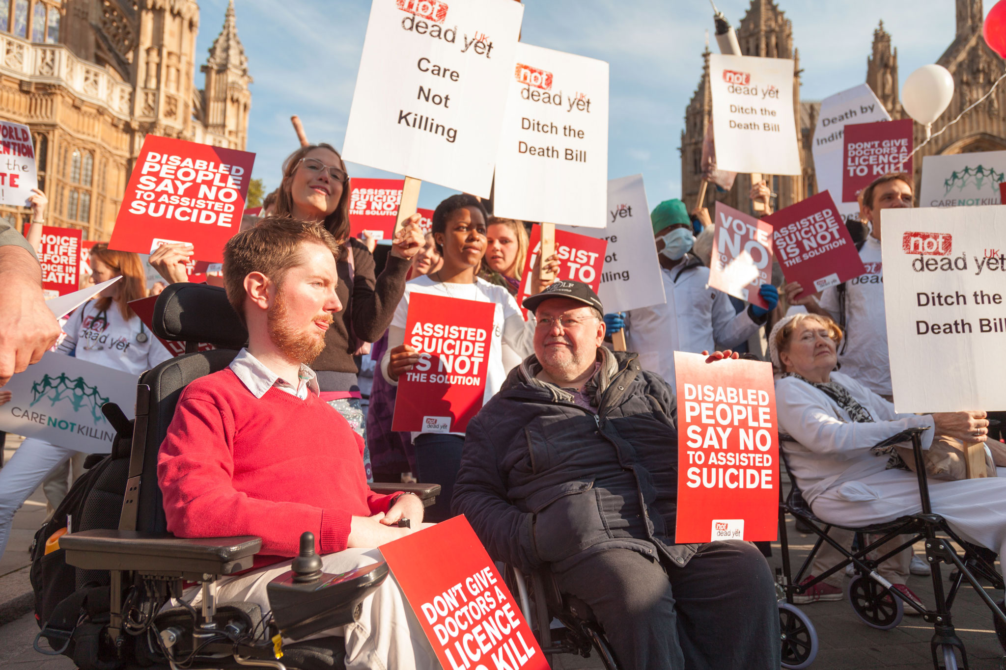 Disability rights advocates carry signs protesting doctor-assisted dying at a rally held by Not Dead Yet UK.