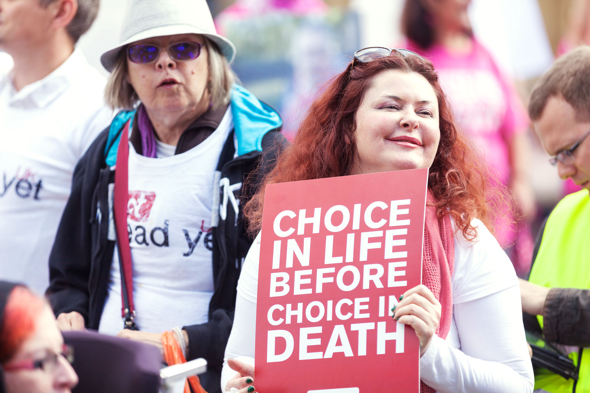 """Supporters of Not Dead Yet UK hold a sign reading """"Choice in Life Before Choice in Death."""""""