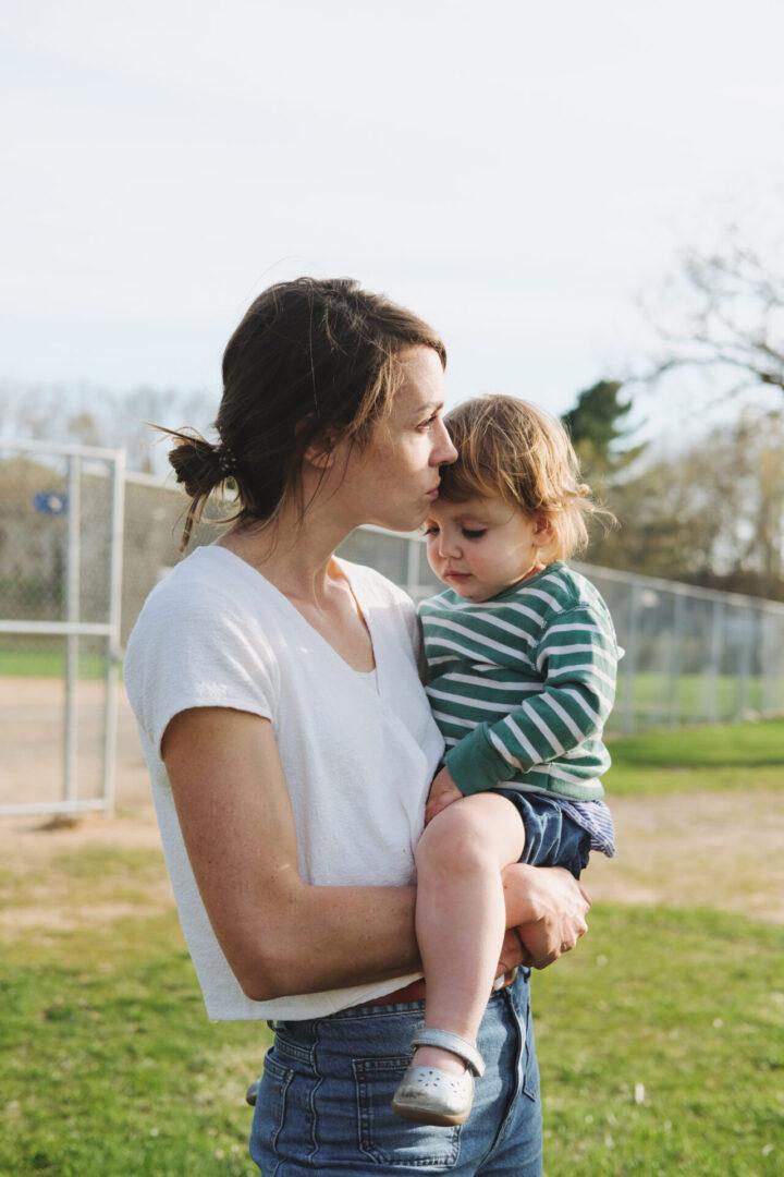Beth holding Willa at baseball diamond