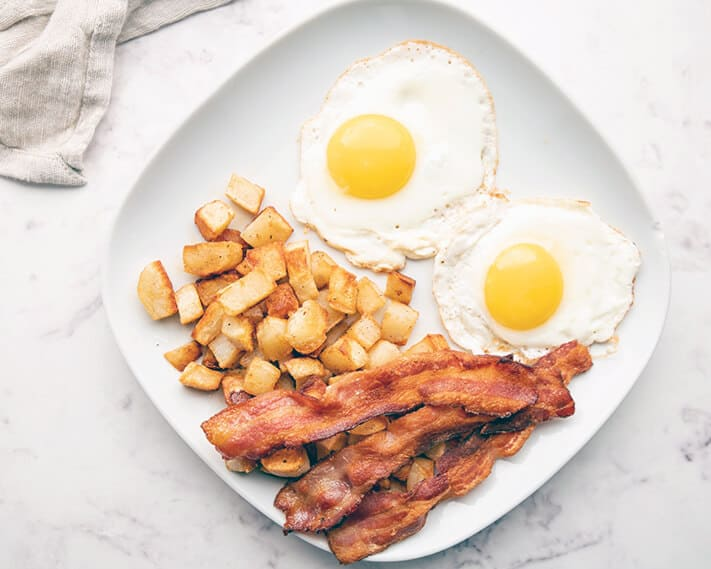 Sunnyside up eggs with bacon and hashbrowns