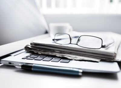 Newspaper on laptop with glasses
