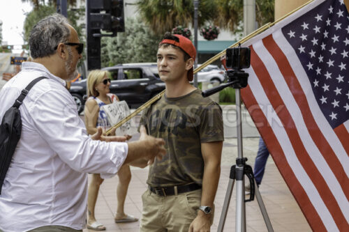 News media interviewing a male protester with American flag