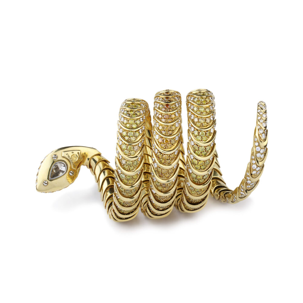 Designed as a flexible gold snake bracelet set with a pear-shaped natural brownish diamond to the head, the coiled body enhanced by yellow diamonds and white diamonds, mounted in yellow gold, circa 1990
