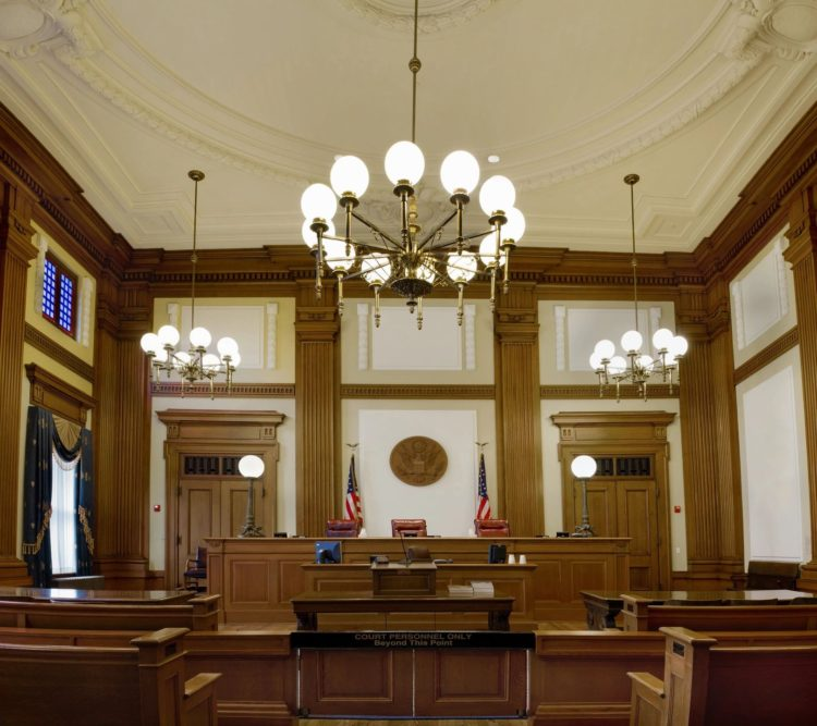 Generic photograph of an empty courtroom with American flags.