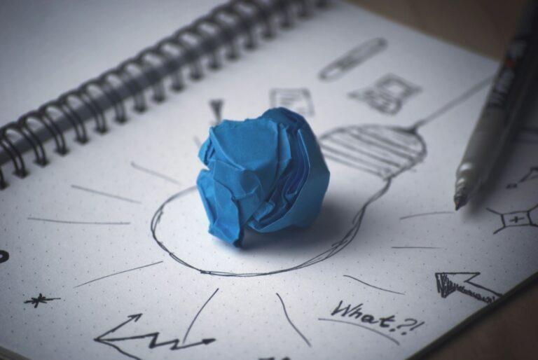 papel amassado sobre desenho de lâmpadas e anotações
