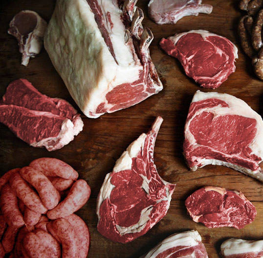 Variety of Fresh Red Meats on a Wooden Board