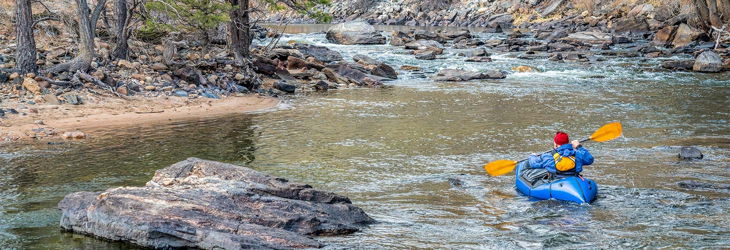Person in an inflatable canoe going downstream in a river