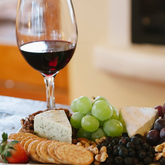 Glass of red wine paired with a plate of assorted cheese and fruit