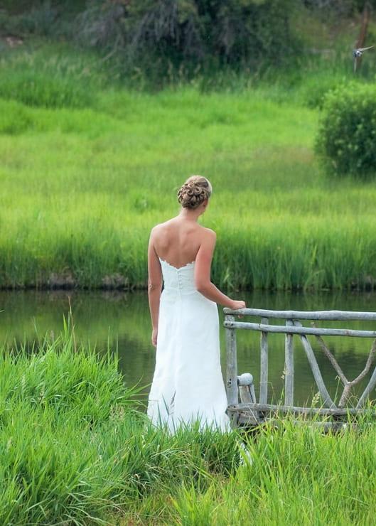 Bride in wedding dress standing near a lake