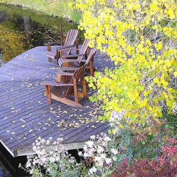 Adirondack chairs on the dock at Blue Lake Ranch with fall foliage.